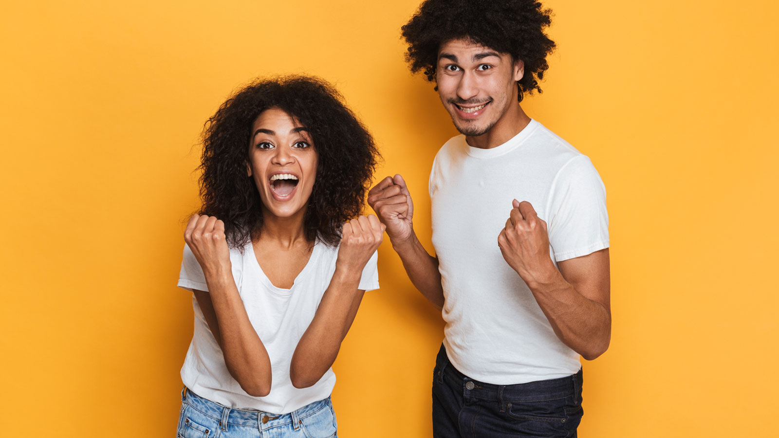 couple jumping for joy on orange background